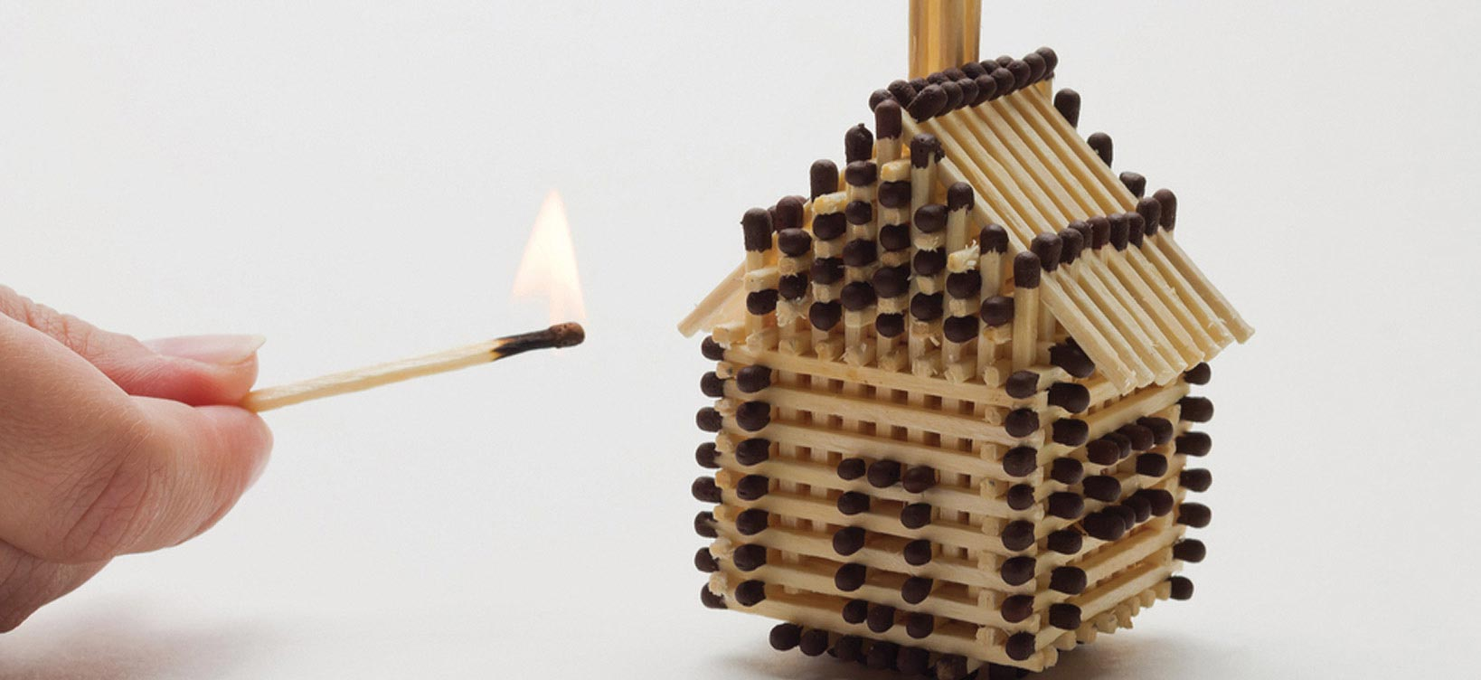 A hand holding a lit match to a little house made from matches